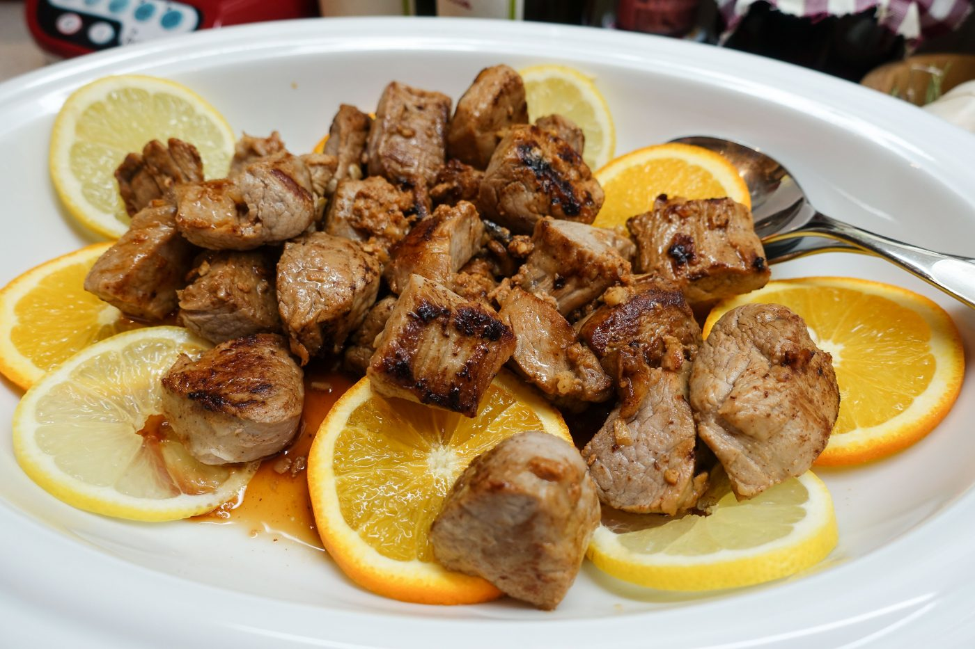 Carne de vinha d'alho - marinated pork with wine-garlic sauce and slices of orange and lemon