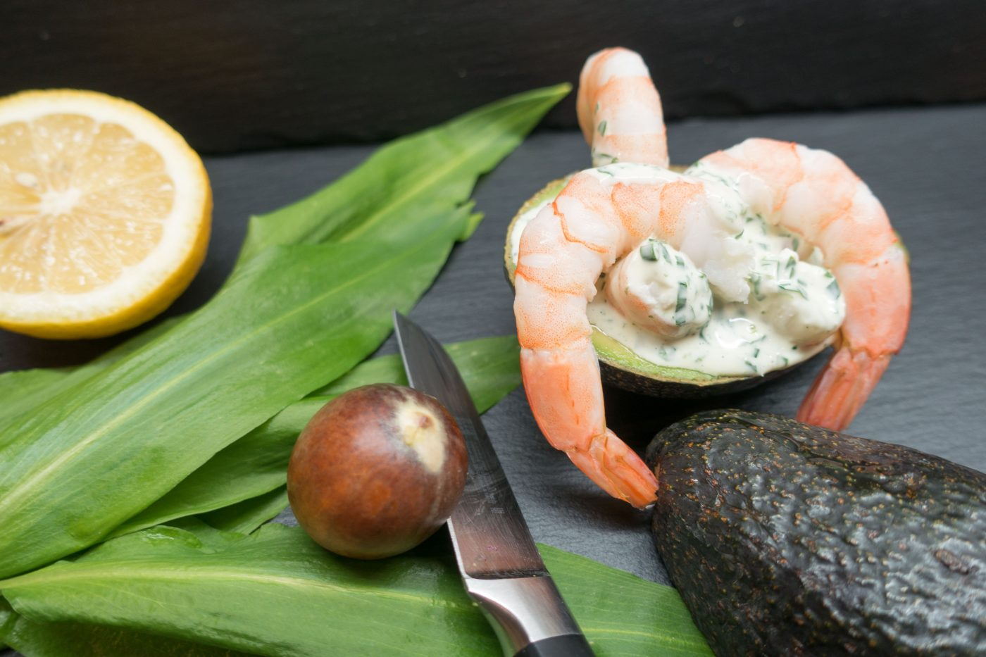 Avocado stuffed with prawns and wild garlic sauce