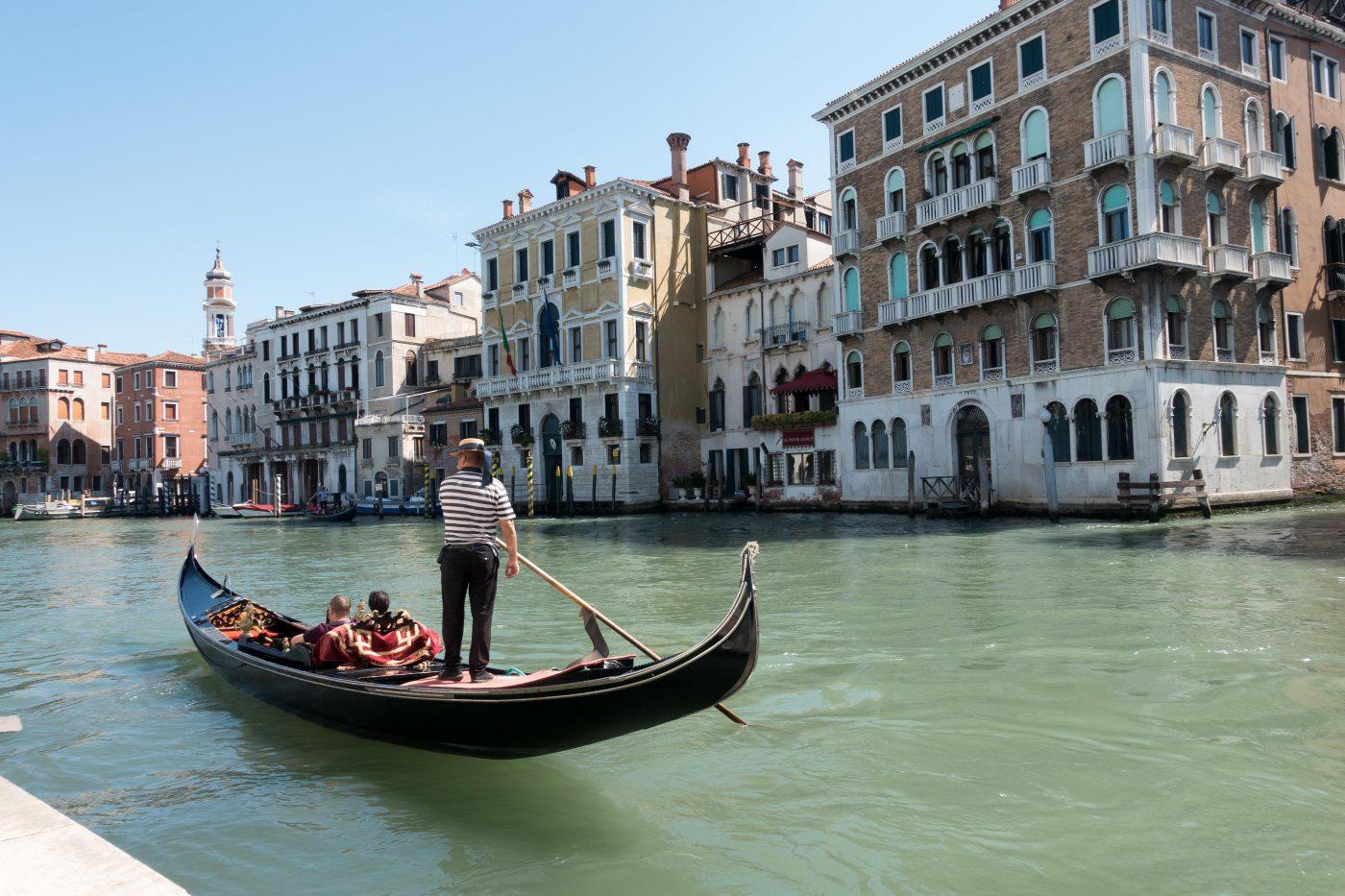Schwarze Gondel mit Gondoliere auf einem Kanal in Venedig