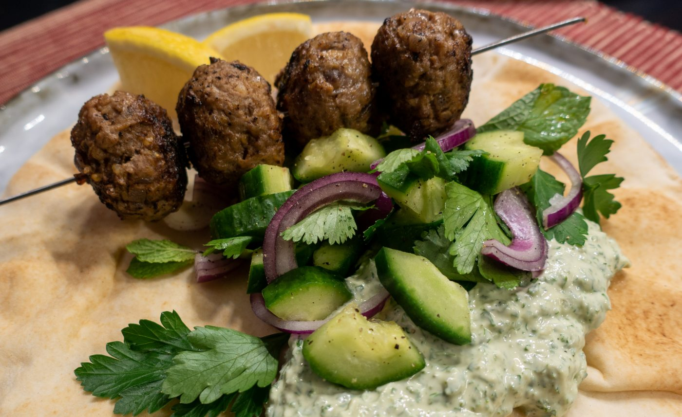 Oriental meatball skewer with kale and yoghurt dip and herb salad on a flatbread