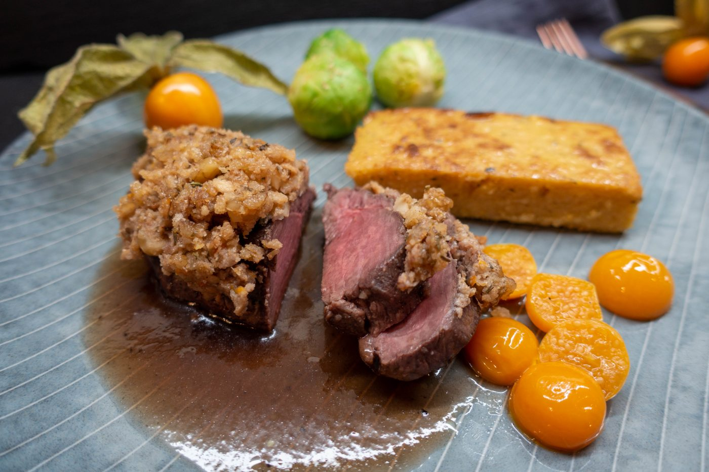 venison fillet under a walnut and herb crust with physalis sauteed in butter, fried polenta slices and an elderberry gravy