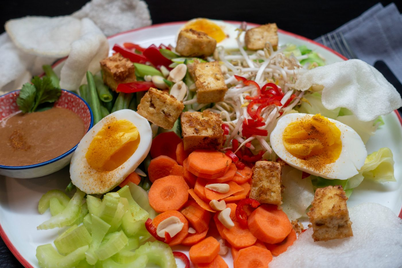 Indonesian Gado Gado, a colorful vegetable plate with boiled egg halves, fried tofu, krupuk and peanut sauce