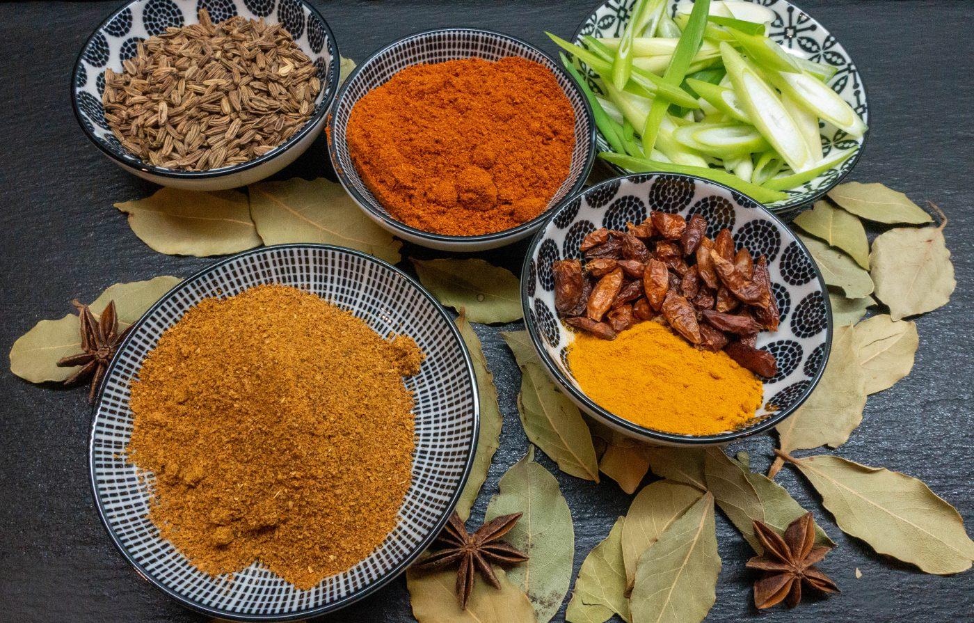 Verschiedene Curry-Gewürze in leuchtend orange-gelben Farben