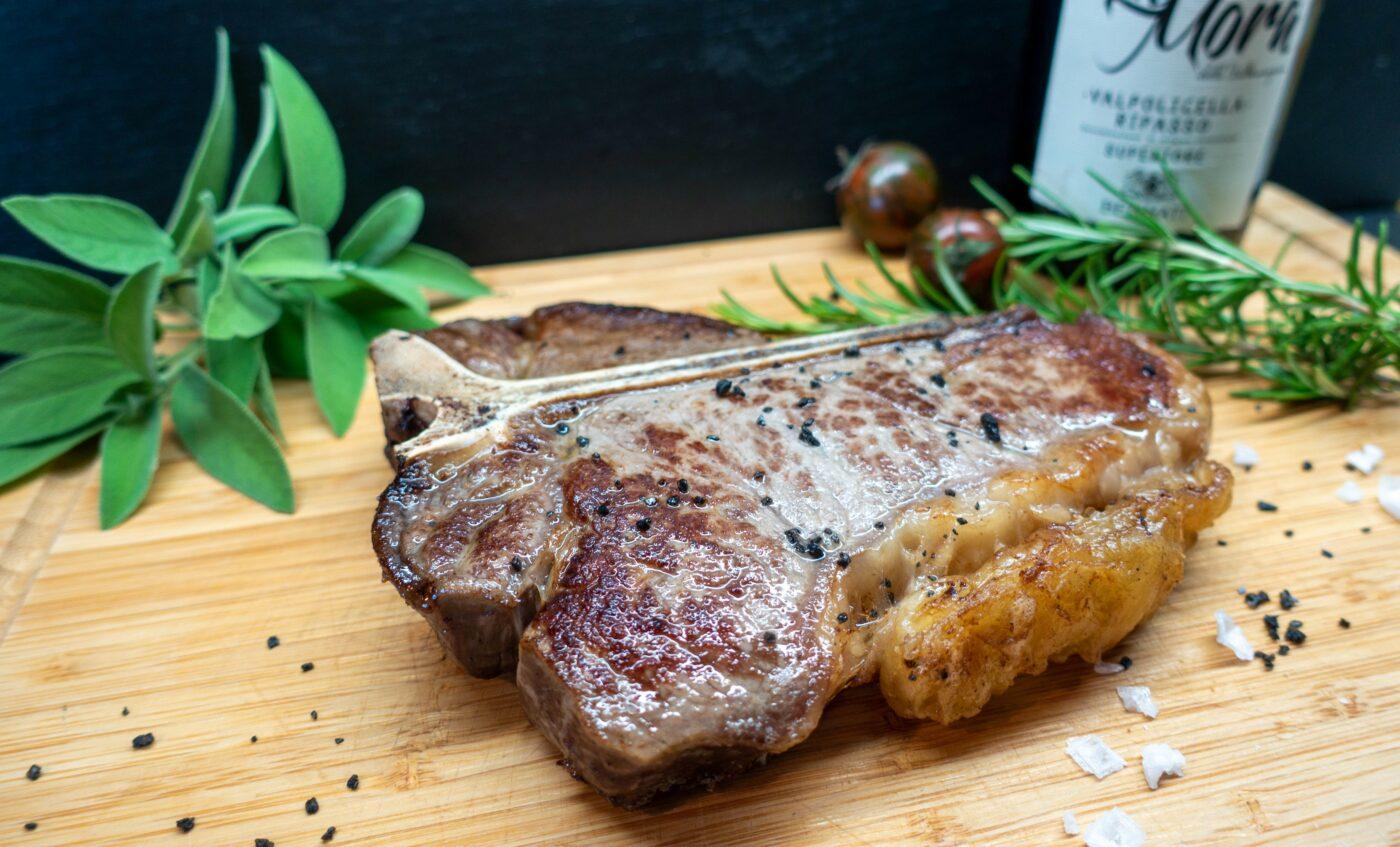 Fried T-bone steak on a wooden board